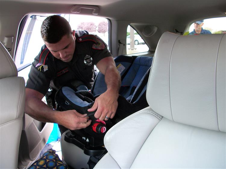 A police officer installing a child safety seat.
